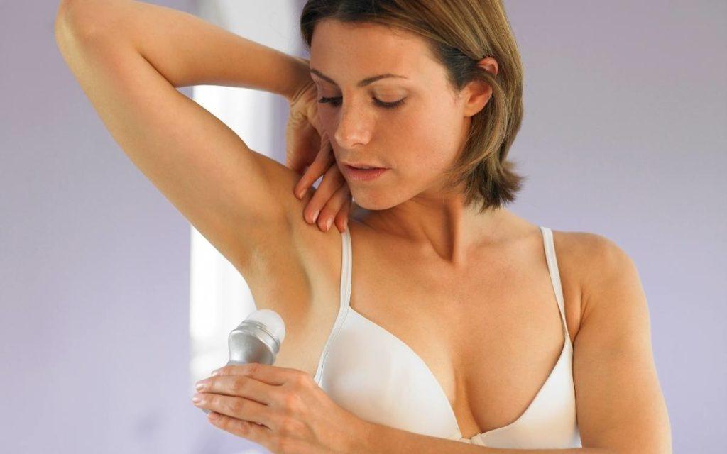 Brunet woman in white bra applying deodorant